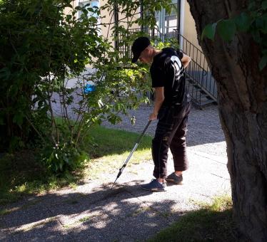En deltagare i arbetskläder rensar mellan stenplattorna.