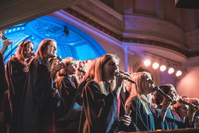 Vasa Gospel på scenen sjungande i mikrofoner