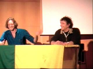 de gebroeders Rueb geamuseerd achter de tafel in de Aula van de Haagse Hogeschool