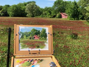 plein air painting with red barn and red clover