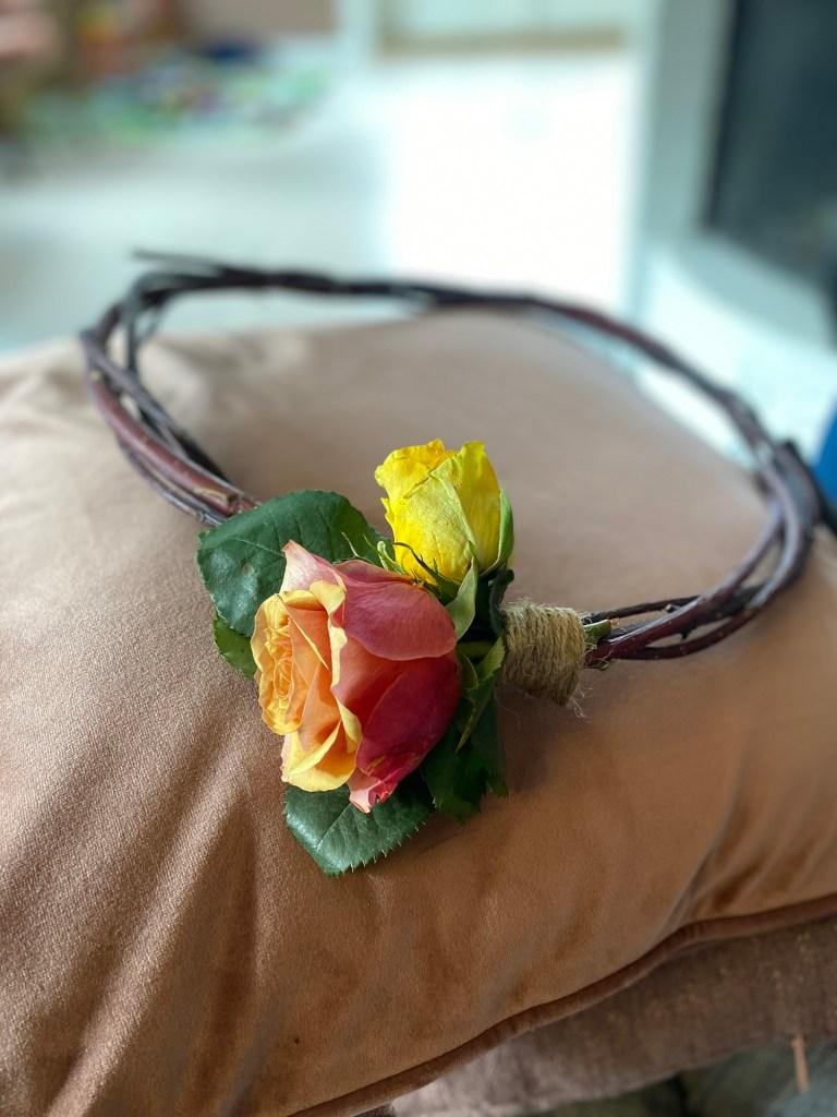 Jutegarn surrer fast rosene til blomsterkransen, kvistkransen