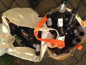 Aufsicht von zwei Stofftaschen, die nebeneinander stehen und mit leeren Glasbierflaschen gefüllt sind.