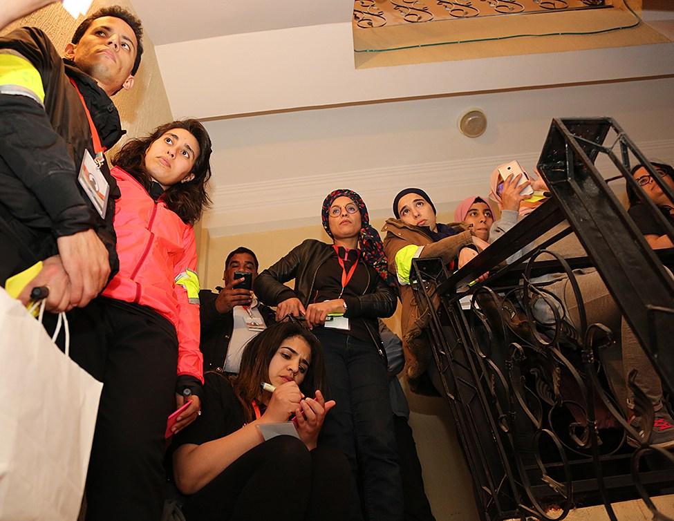 Eine Gruppe von jungen Teilnehmern mit konzentrierten Blicken steht im Treppenhaus