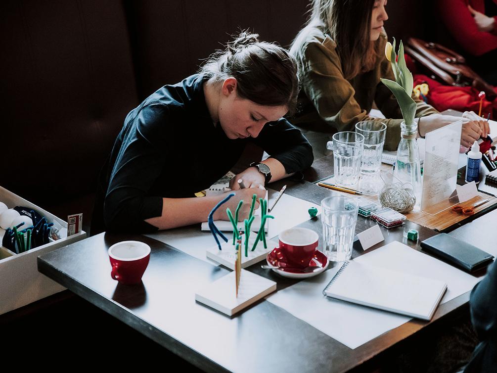 Eine Workshop-Teilnehmerin sitzt am Tisch und schreibt in einen Block.