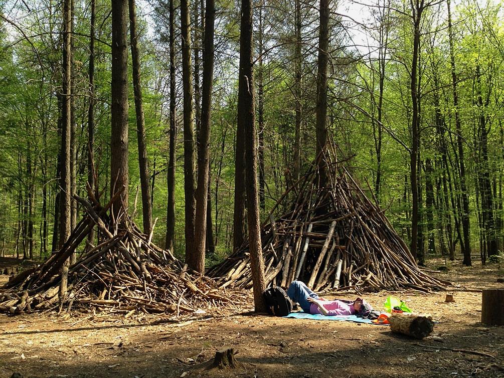 Auf eine Waldlichtung liegt eine Frau auf einer Picknickdecke und macht ein Nickerchen. Im Hintergrund befinden sich zwei aus Ästen gebaute Höhlen. Die Bäume weisen frisches, grünes Laubwerk auf.