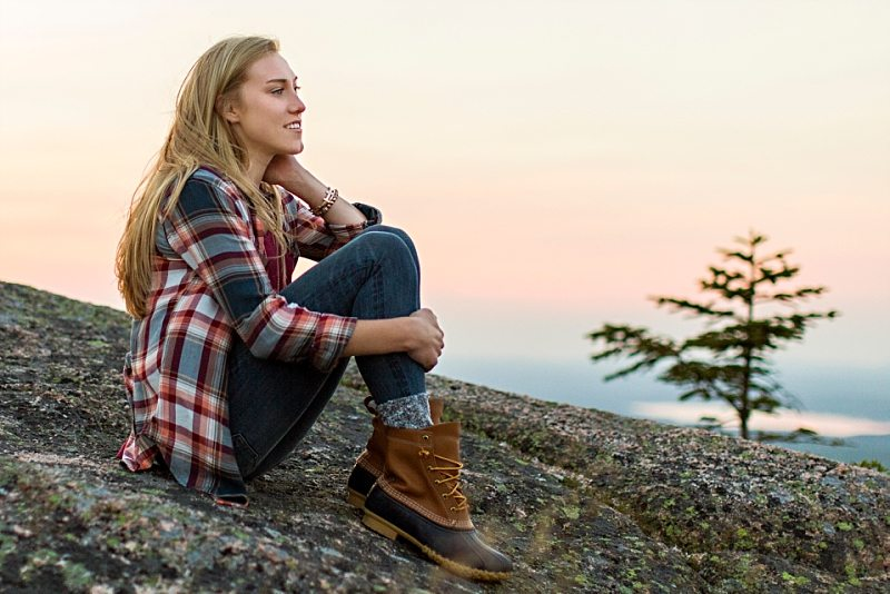 A senior portrait of a girl sitting on Cadillac Mountain at sunset.