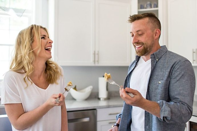 A lifestyle photo of a couple laughing and eating pancakes together in their kitchen.