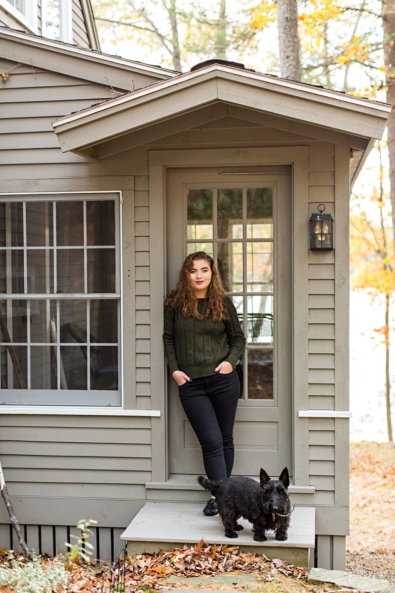 A girl poses against a door with her Scottie dog for her senior portraits.