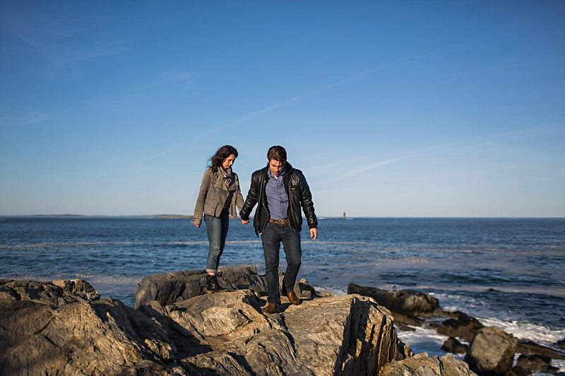 A couple walks together on the cliffs at Portland Head Light.