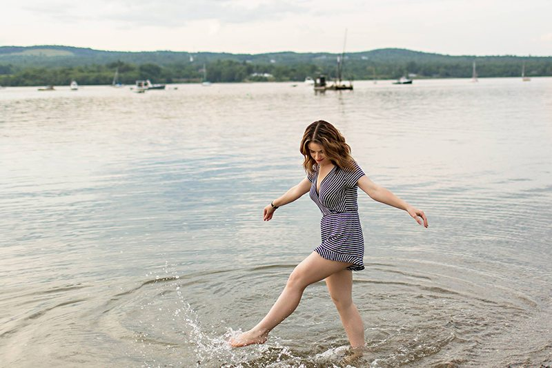 A woman wears a romper and splashes around in the ocean.