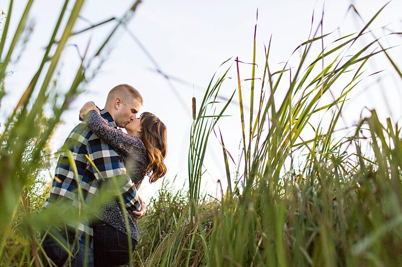 A portrait of a couple kissing, photographed through blades of grass.