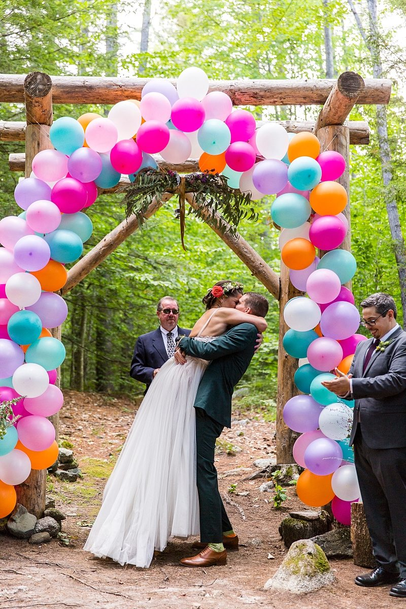 A groom lifts the bride during their first kiss under a balloon-covered arbor.