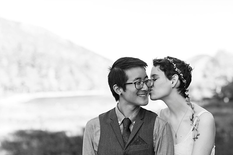 A black and white portrait of a bride kissing the groom on the cheek at Jordan Pond in Acadia National Park.