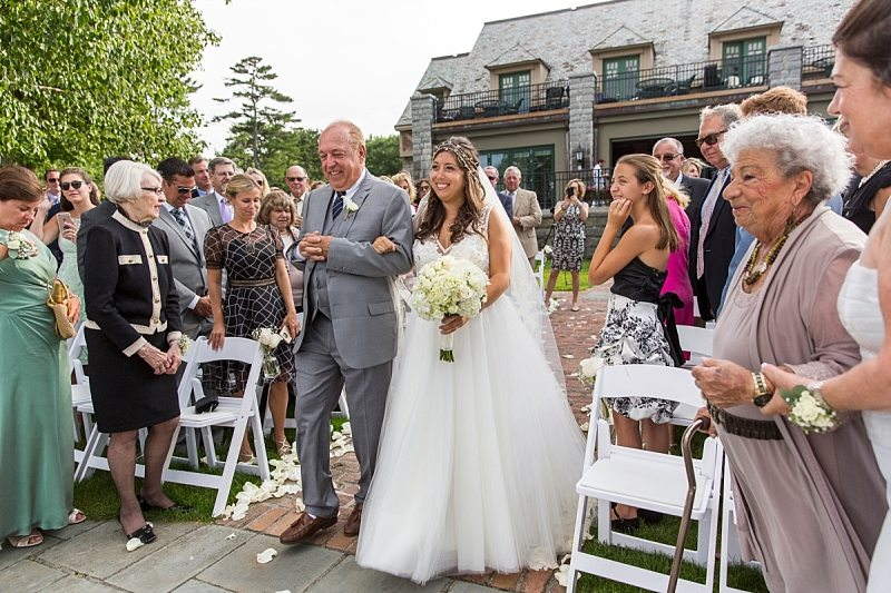 The bride and her father happily walk down the aisle for the wedding ceremony at The Regency in Bar Harbor, Maine.