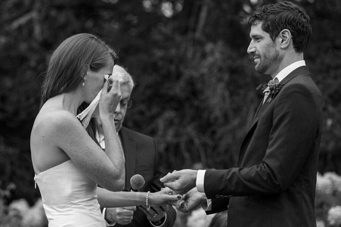 A black and white photo of a bride wiping her tears with the handkerchief the groom has just handed her during the ceremony.