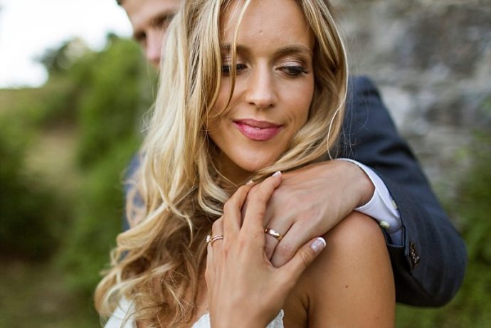 A close up of a bride's face as she holds the groom's hand on her shoulder, showing off both wedding bands.