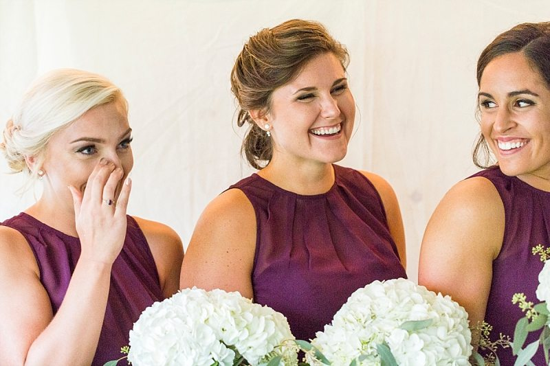 Three bridesmaids start laughing immediately after crying during the groom's vows at Flanagan Farm in Maine.