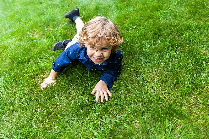 A little boy at a wedding crawls in the grass and smiles at the camera.