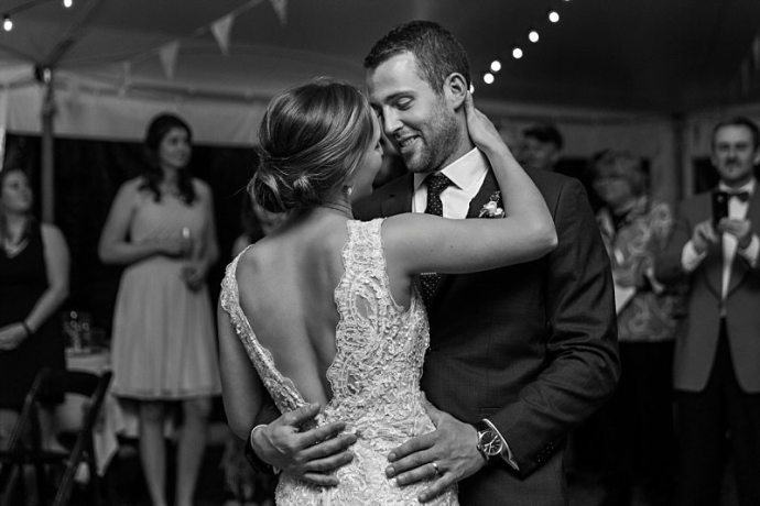 A black and white image of a couple dancing their first dance at their wedding after ten years together. They smile and look deep into each other's eyes.