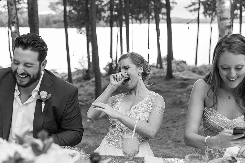 The bride, groom, and maid of honor laugh heartily after the best man drops his pants during his wedding toast.