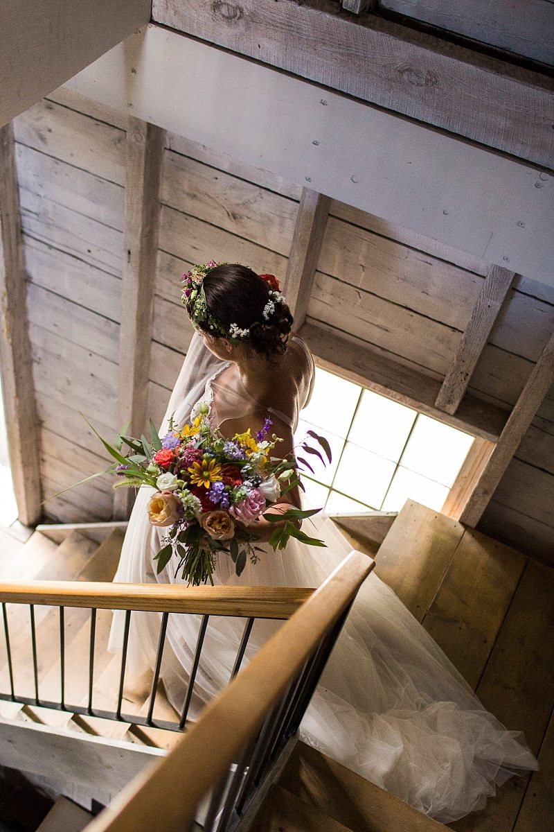 A bride descends the stairs in a beautiful, white-washed barn carrying her bouquet with sunlight falling on her.
