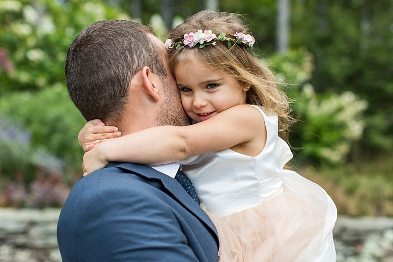 The groom carries the flower girl as she hugs him tightly around the neck.