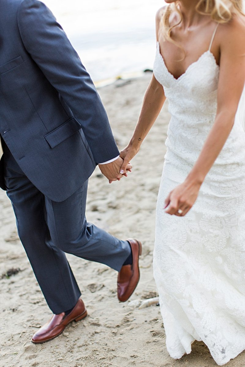 A close up of a bride and groom's hands. They hold hands as they walk together on the beach.