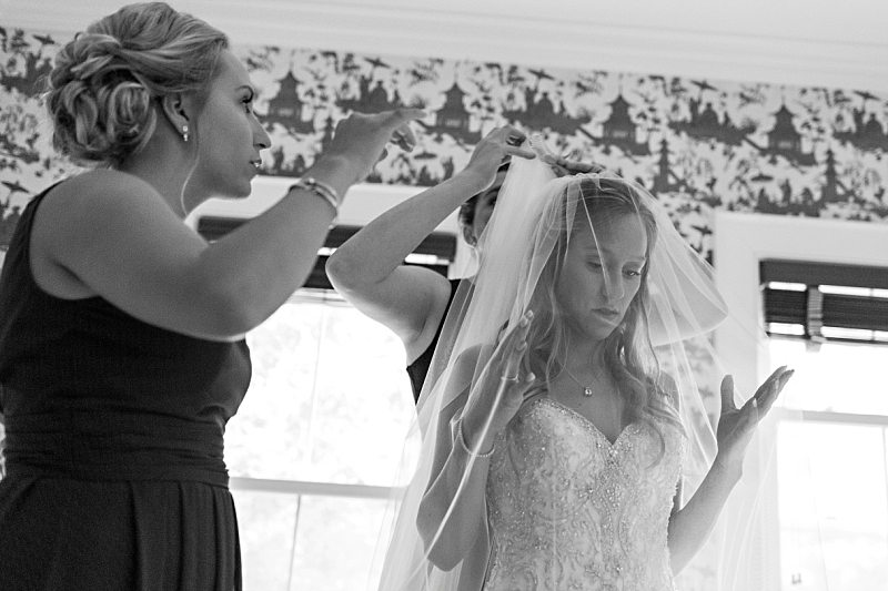 A black and white photo of a bride's sister and future sister-in-law placing her veil in her hair.