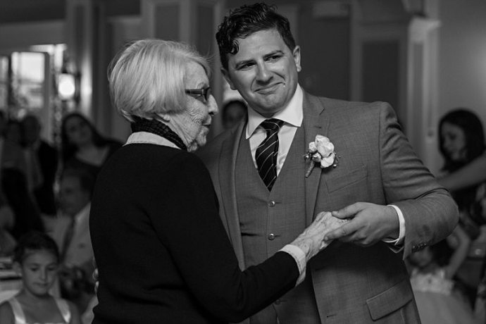 An emotional black and white photo of a groom crying as he dances with his grandmother at his wedding reception.
