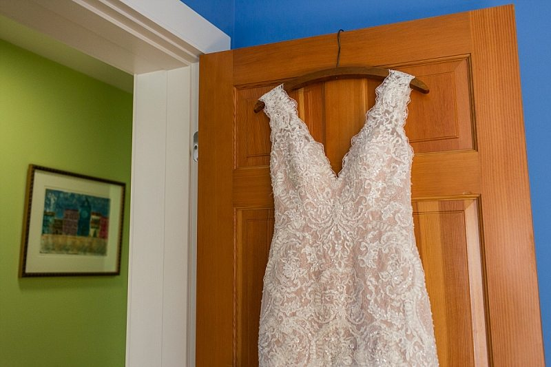 A wedding dress hangs on a door with bright blue and green walls around it.