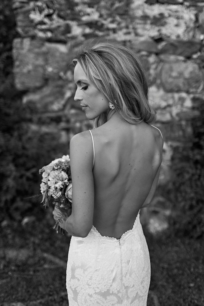 A black and white portrait of a bride looking over her shoulder with in a backless wedding gown.