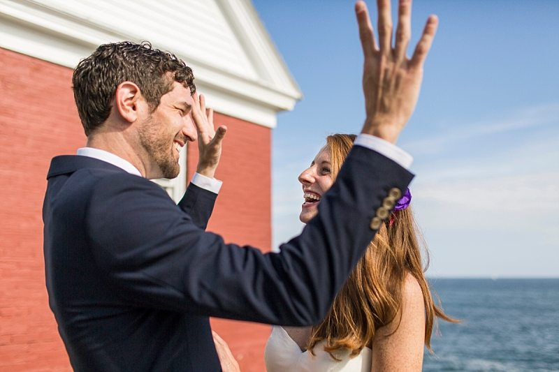 A groom raises his hands in the air in excitement as he looks at the bride.