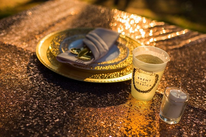 Sunlight shines on the tablecloth, place setting and through a cup creating a golden glow. The cup states the name of the couple and their wedding date.