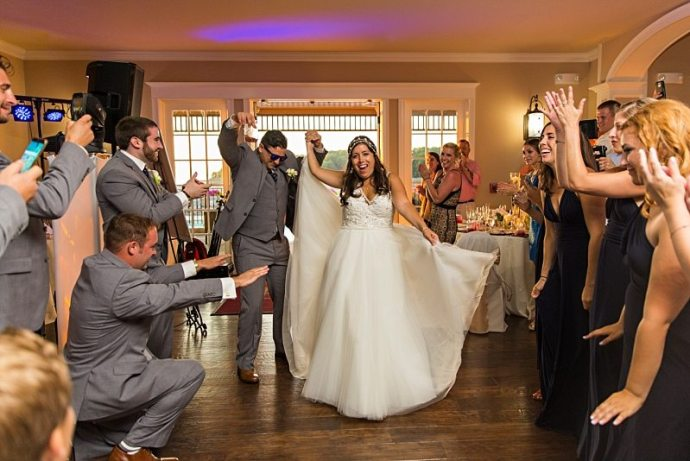 A wedding party cheers as the bride and groom dance their way into the reception.
