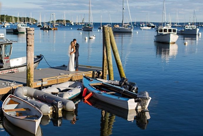 A bride and groom embrace in a scenic shot showing Rockport Harbor in Maine.