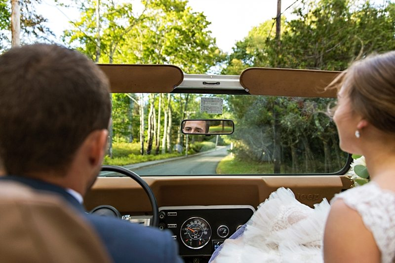 The bride and groom ride together as they head out for wedding portraits. The focus is on the groom's eyes in the rear-view mirror.