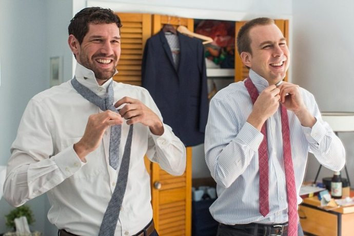 A groom and his best man laugh as they struggle to tie their ties.