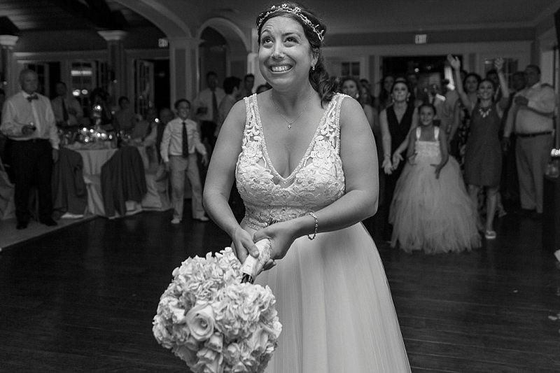 A bride smiles widely as she stats to throw her bouquet.