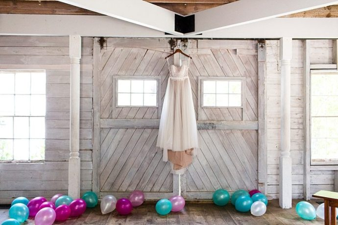 A wedding dress hangs in the white-washed barn at Hardy Farm surrounded by balloons.