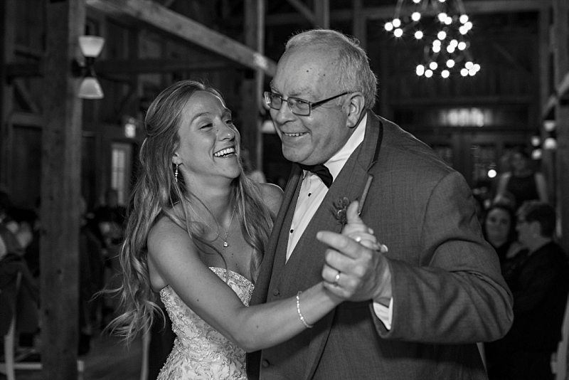 A bride and her father laugh as they dance together at the reception.