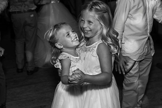 Two flower girls dance together and laugh at a wedding reception.