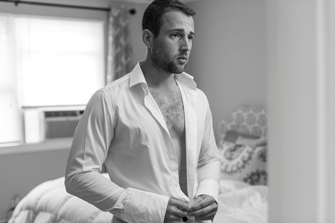 A groom buttons up his shirt as he looks in the mirror.