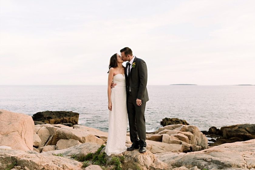 Bride and groom kiss at Otter Point in Acadia National Park.