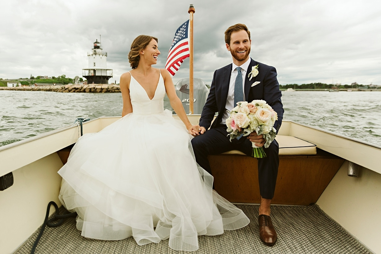 A bride and groom laughing on a boat on the way to their Peaks Island Maine wedding