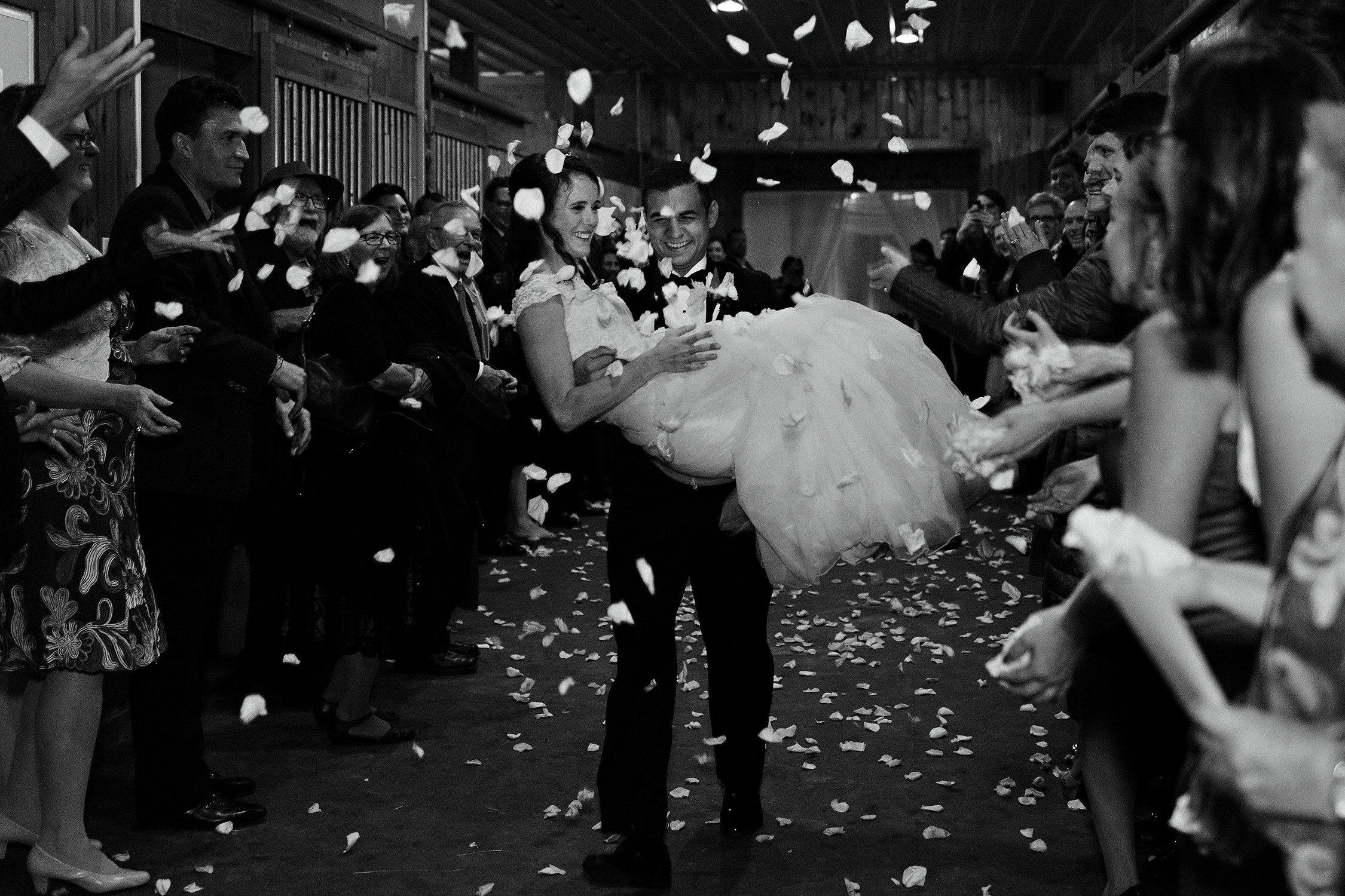 Groom carries bride through petal toss