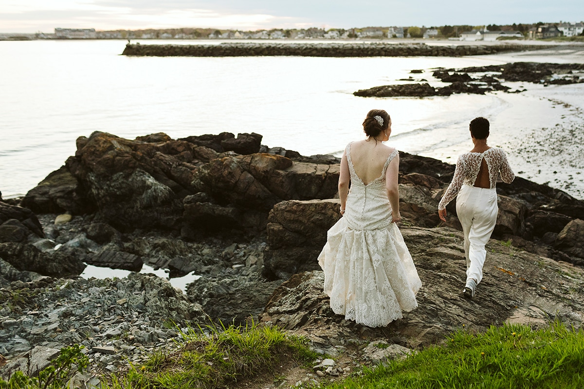 Two brides on rocky coast at sunset