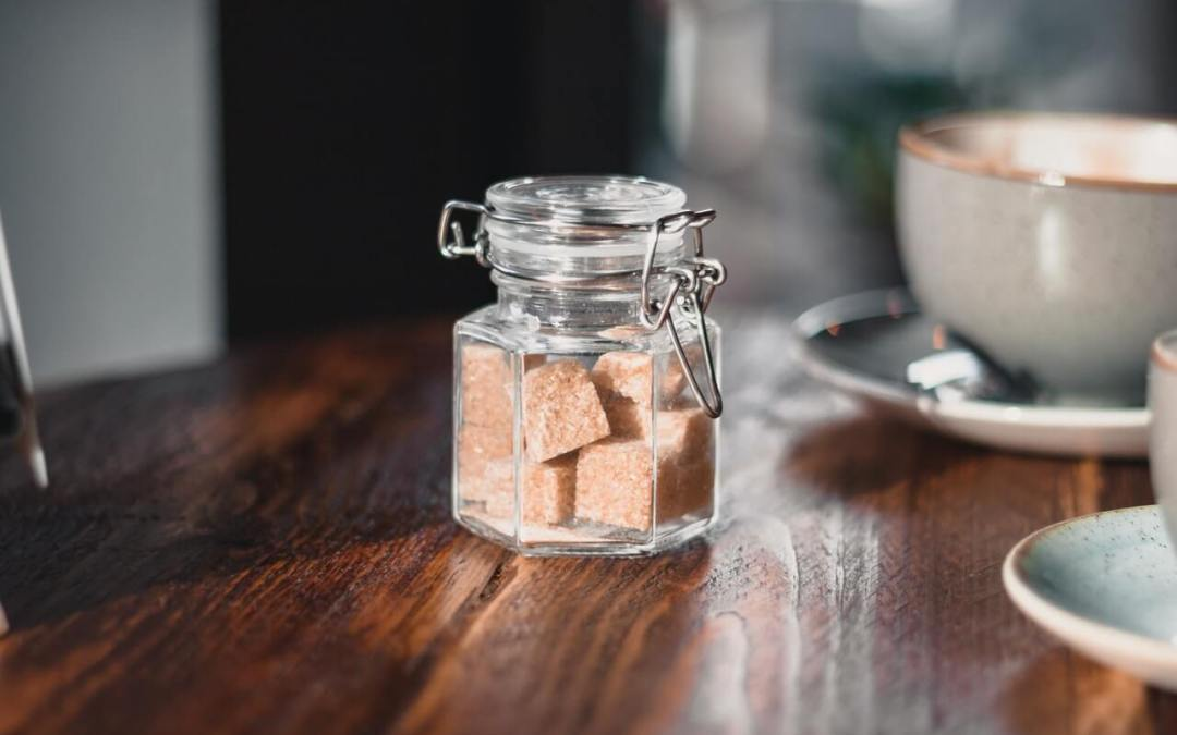 clear-condiment-shaker-with-brown-sugar-cubes-near-gray