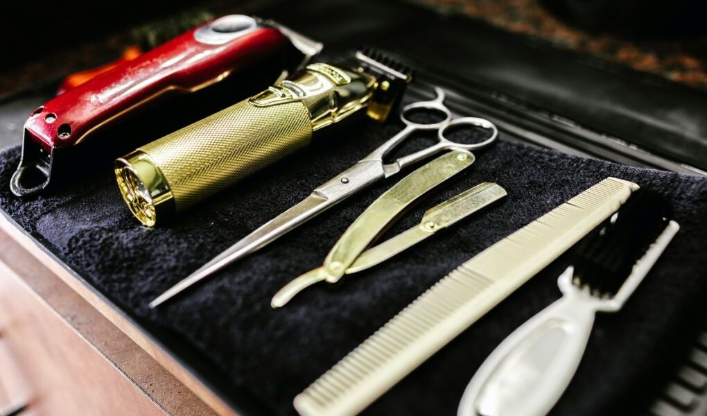 stainless steel scissors beside red and silver pocket knife