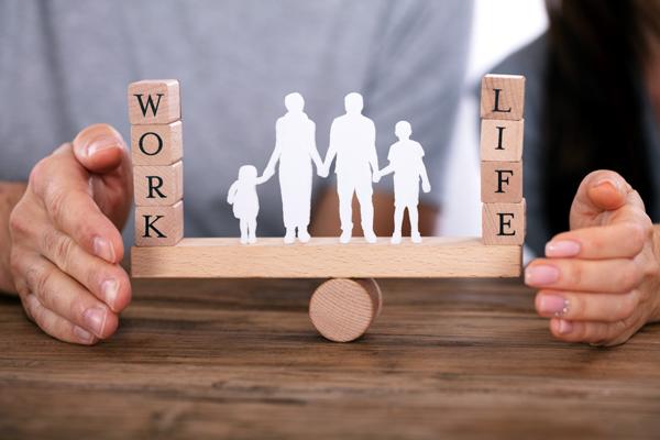 仕事と生活のバランスを守るカップル、シーソーの上に立つ家族の姿