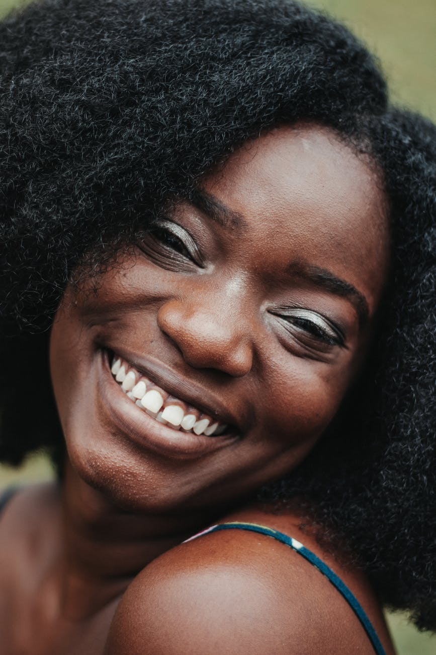 cheerful black woman with wavy hairstyle smiling